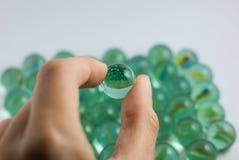 拿着绿色大理石球 免版税库存照片