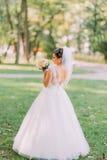 拿着黄色婚礼花束的后面观点的新娘在公园的背景 库存图片