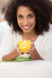 拿着黄色存钱罐的微笑的妇女 免版税图库摄影