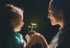 拿着绿色新芽的成人和孩子 库存图片