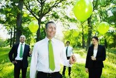 拿着绿色气球的环境友好的商人在森林 免版税库存图片
