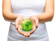 拿着绿色球形地球的妇女手 库存照片