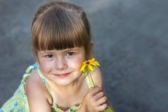 拿着黄色花的逗人喜爱的微笑的小女孩 库存图片