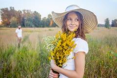 拿着黄色花花束和看与她的男朋友的美丽的妇女照相机背景的 库存图片