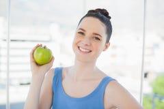 拿着绿色苹果的运动服的快乐的苗条妇女 免版税库存图片