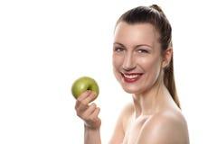 拿着绿色苹果计算机的俏丽的妇女反对白色 免版税库存照片