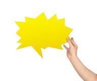 拿着黄色讲话泡影的手 免版税库存图片