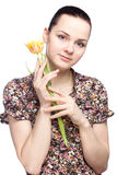 拿着黄色郁金香的可爱的少妇 免版税库存图片