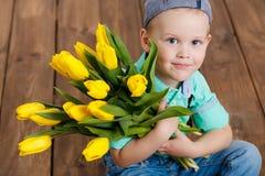 拿着黄色郁金香的花束微笑的男孩在手上坐木地板 图库摄影