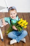 拿着黄色郁金香的花束微笑的男孩在手上坐木地板 库存图片