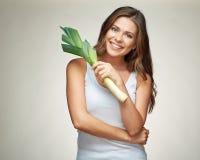 拿着绿色韭葱的愉快的微笑的妇女 免版税图库摄影