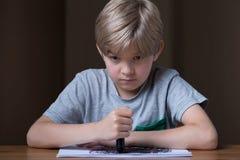 拿着黑蜡笔的不快乐的孩子 免版税库存图片