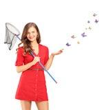 拿着蝴蝶网和蝴蝶的微笑的年轻女性 免版税库存照片