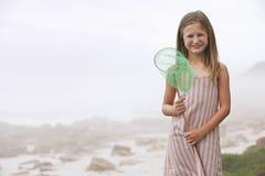 拿着蝴蝶网的女孩在海滩 库存照片