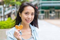 拿着蝴蝶薄脆饼干的妇女 库存照片