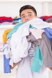 拿着洗衣店的年轻微笑的人 免版税库存照片