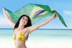 拿着巴西旗子的可爱的妇女 免版税库存照片