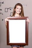 拿着画象框架的愉快的女孩 图库摄影