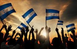 拿着洪都拉斯的旗子的人剪影  免版税库存图片