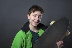 拿着他长的委员会的骄傲的微笑的十几岁的男孩 免版税库存图片