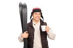 拿着滑雪和喝热的茶的年轻人 免版税库存图片