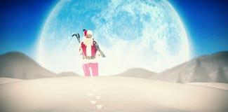 拿着滑雪和滑雪杆的圣诞老人的综合图象 库存图片