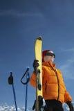 拿着滑雪的冬天夹克的妇女反对蓝天 库存照片
