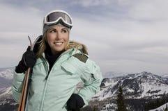 拿着滑雪的女性滑雪者 免版税库存图片