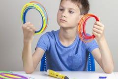 拿着3d笔的孩子五颜六色的细丝和选择新的项目的颜色 免版税图库摄影