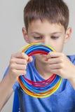 拿着3d笔的孩子五颜六色的细丝和选择新的项目的颜色 免版税库存图片