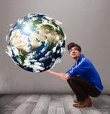 拿着3d行星地球的俊男 免版税库存照片