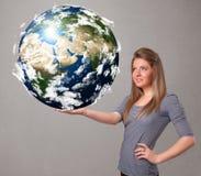 拿着3d行星地球的俏丽的女孩 免版税库存图片
