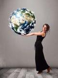 拿着3d行星地球的俏丽的女孩 库存照片