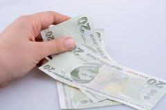 拿着20 Turksh里拉钞票的手手中 免版税库存照片