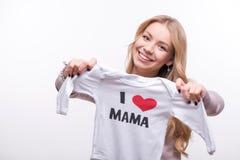 拿着babysuit的年轻可爱的妇女我爱妈妈 库存照片