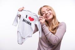 拿着babysuit的年轻可爱的妇女我爱妈妈 免版税图库摄影