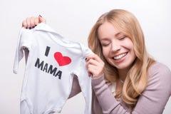 拿着babysuit的年轻可爱的妇女我爱妈妈 图库摄影