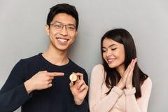 拿着bitcoin的快乐的年轻亚洲爱恋的夫妇 免版税图库摄影