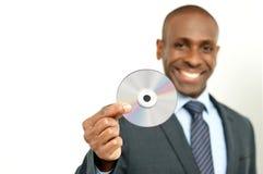 拿着cd的英俊的商人 免版税库存照片