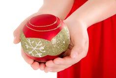 拿着christmass装饰品的儿童手 库存图片