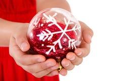 拿着christmass装饰品的儿童手 库存照片