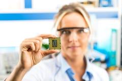 拿着CPU的年轻女性电子工程师手中 免版税库存图片