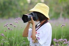 拿着DSLR照相机和站立在花背景,旅行生活方式假期概念的年轻女人在他的手上 库存图片