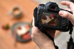 拿着dslr照相机的摄影师的手拍照片 库存图片