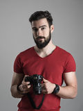 拿着dslr的红色衬衣的年轻有胡子的摄影师看照相机 免版税库存照片