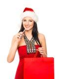 拿着e香烟的圣诞节帽子的一名愉快的妇女 免版税库存图片