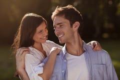 拿着eachother的年轻夫妇在公园 免版税库存图片