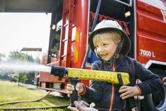 拿着firehose喷管和飞溅水的小消防员 免版税库存图片