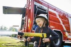 拿着firehose喷管和飞溅水的小消防员 库存图片