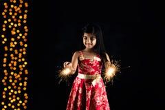 拿着fulzadi或闪闪发光或者火薄脆饼干的印地安小女孩储蓄照片在diwali夜 库存图片